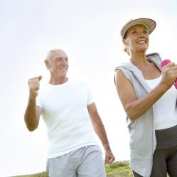A happy elderly couple doing some exercise outdoors together